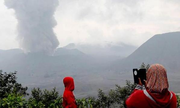 Dua orang sedang memfoto Gunung Bromo Meletus