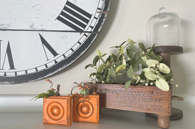 Cheese box and small wooden pumpkins on the mantel