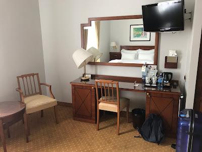 Skrivebord, to stoler, et stort speil og en tv festet på veggen.