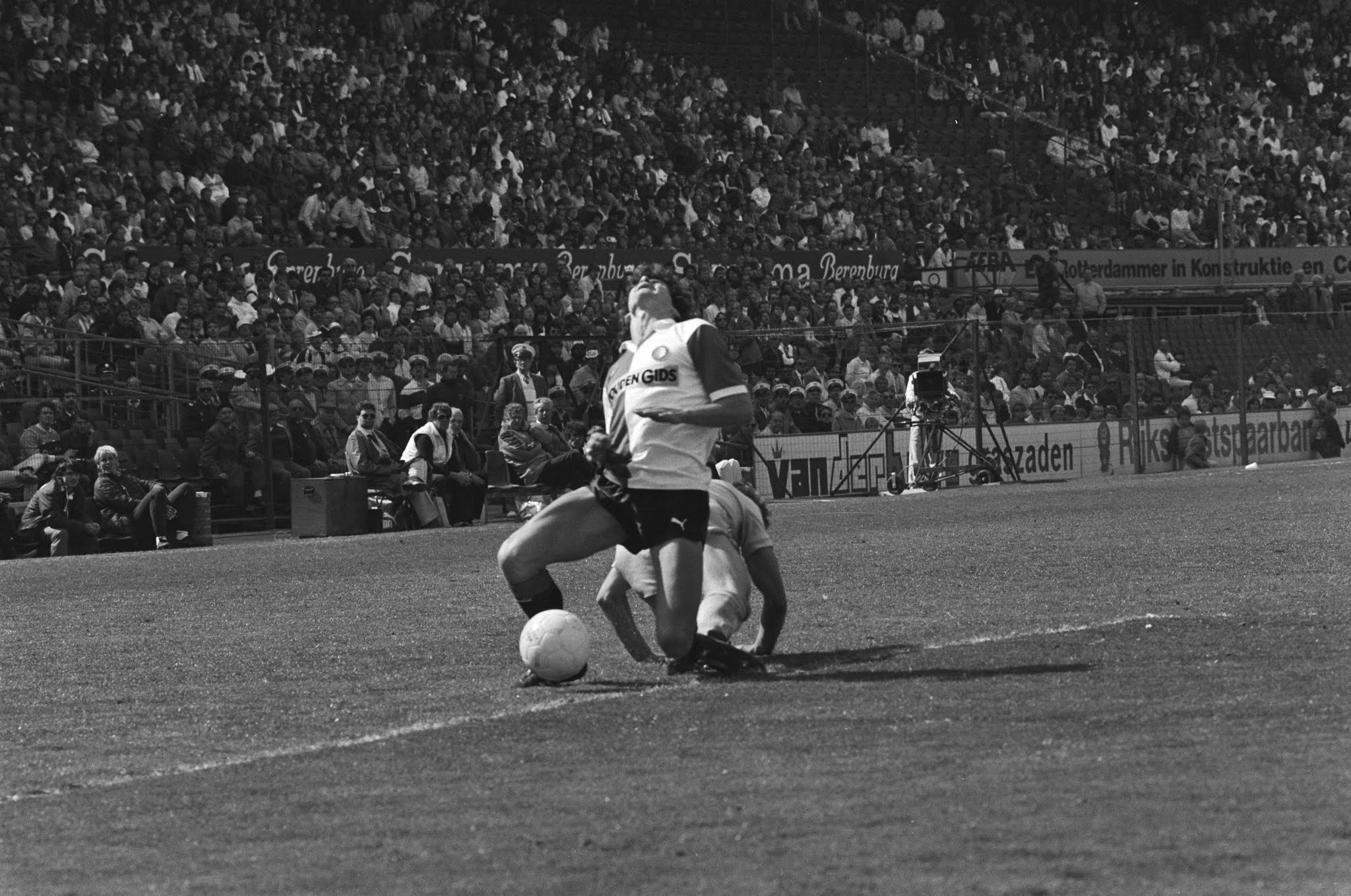 Sjaak Troost (Feyenoord) onderuitgeschoffeld door Ben Rietveld (Utrecht)