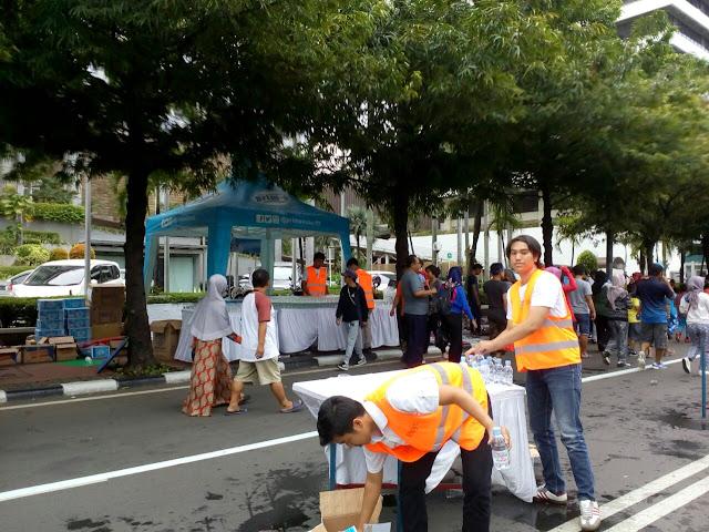 Panitia menyiapkan air minum bagi peserta lari