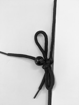 Backbeat Maze - Close up of the book binding shoe lace and tiny ball.