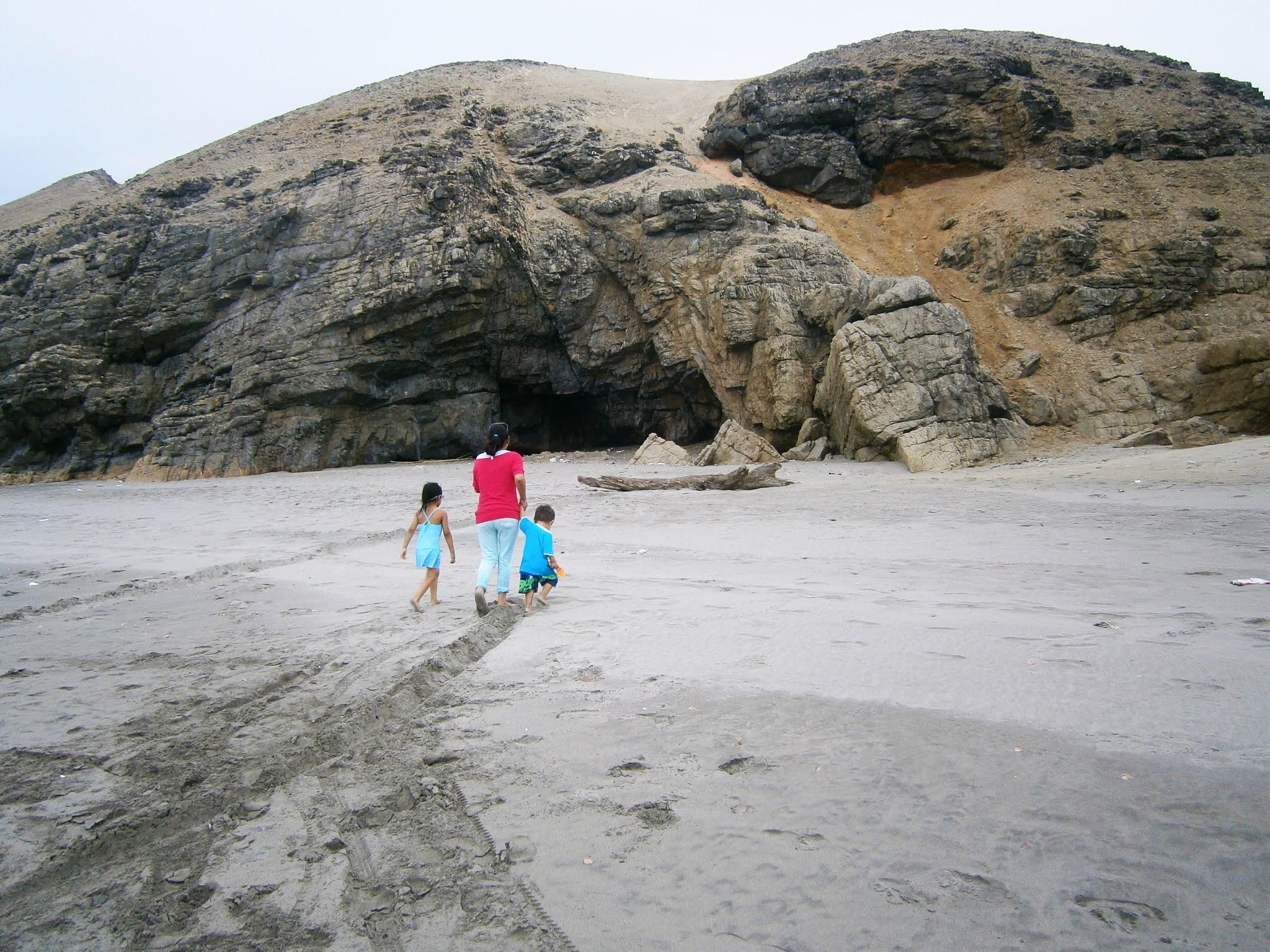 Mujer peruana y adulta caminando sobre la arena frente a la playa