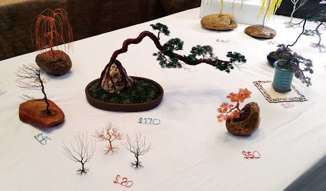 Miniature trees made of twisted coloured wire create bonsai landscapes against a white tablecloth backdrop.
