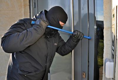 صورة للص مقنع يحول خلع أحد الأبواب