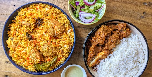 A plate of chicken biryani and another one with goat karahi shown together