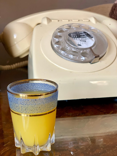 orange juice in glass next to vintage telephone