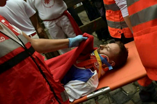 an injured man taken on a stretcher during the running of the bulls.