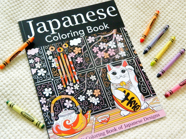 Japanese Colouring Book, the cover is black with cherry blossoms on, a lucky cat, a tea set and a wind chame