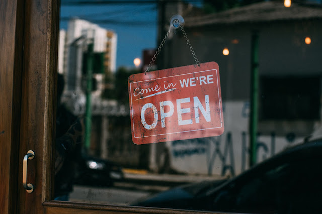 """A retail store's """"OPEN"""" sign on display by the shop's door."""