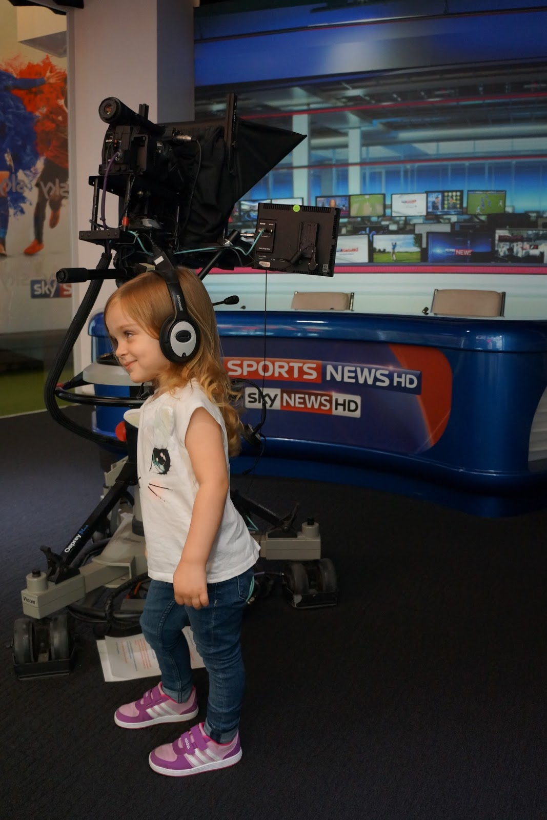toddler wearing headphones at the sky studios at the o2 news desk