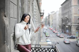 Mujer en un balcón, revisando sus redes sociales.
