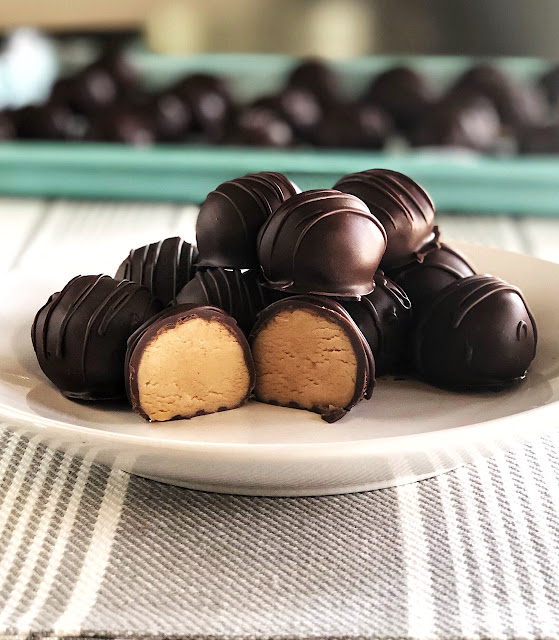peanut butter balls stacked on a white plate