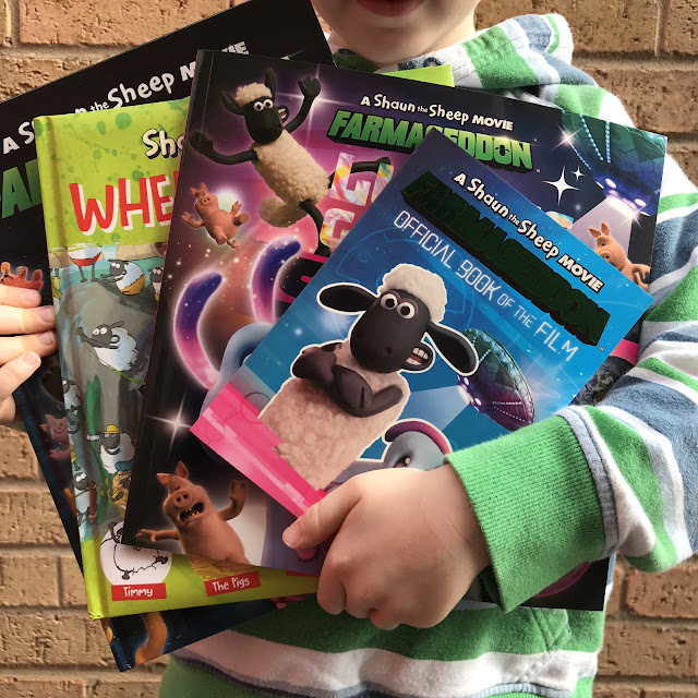 Little boy holding a selection of Shaun the Sheep books