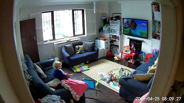 Still image of living room from indoor security camera showing children watching TV