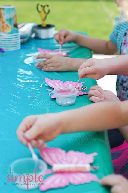 Use q-tips to spread glitter glue on the wings of this fairy party birthday party craft.