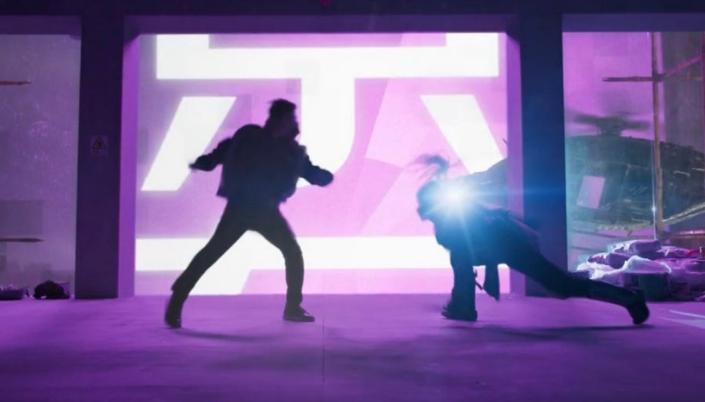 Imagem: fundo com um anúncio de néon cor de rosa com caracteres chineses e as silhuetas de Shang-Chi lutando com um guerreiro mascarado em um andar de um prédio.