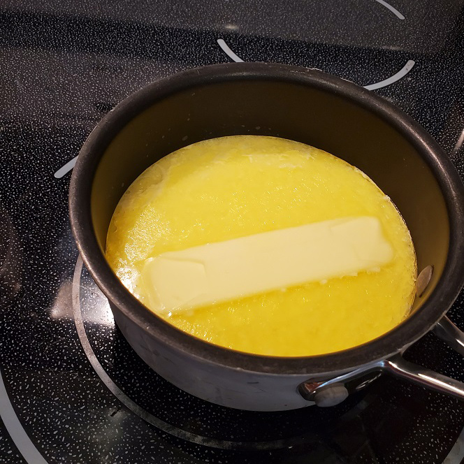 this is a pot of warm milk with a stick of butter melting in a pot for ice milk