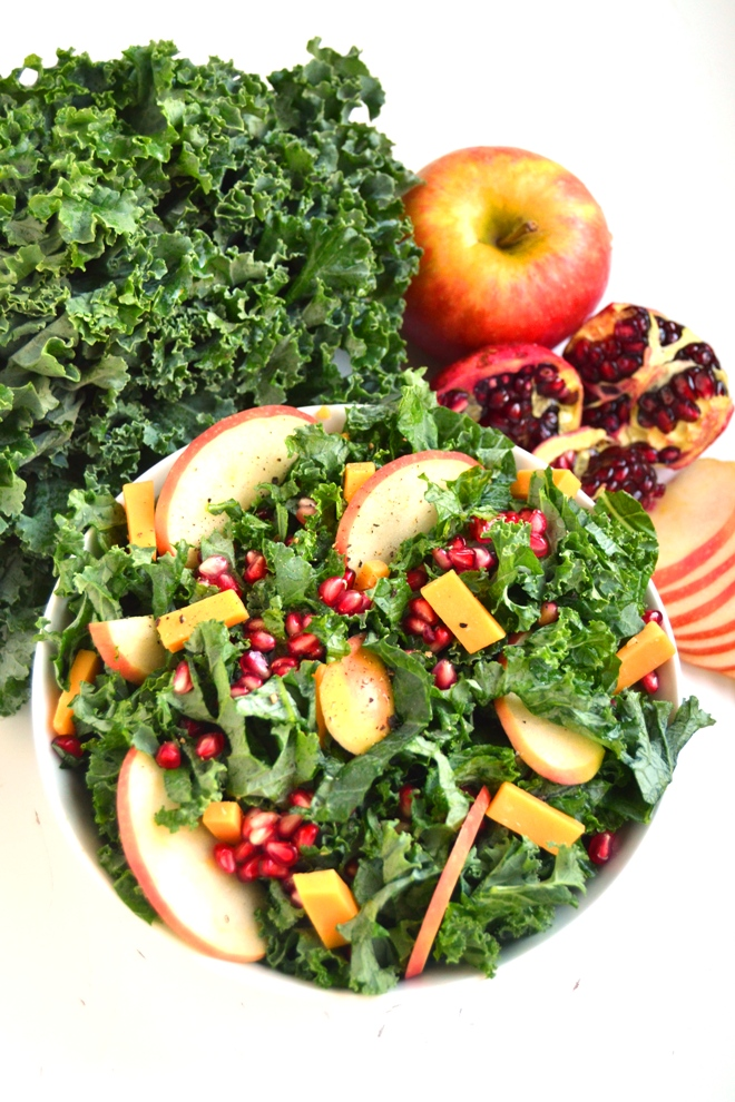 Kale Salad with Pomegranate, Cheddar and Apples features fresh kale, pomegranates, apples and cheddar cheese with a homemade apple cider vinaigrette for the perfect hearty salad! www.nutritionistreviews.com