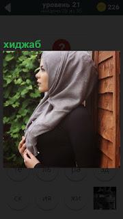 Около стены стоит девушка одетая на голове в хиджаб серого цвета