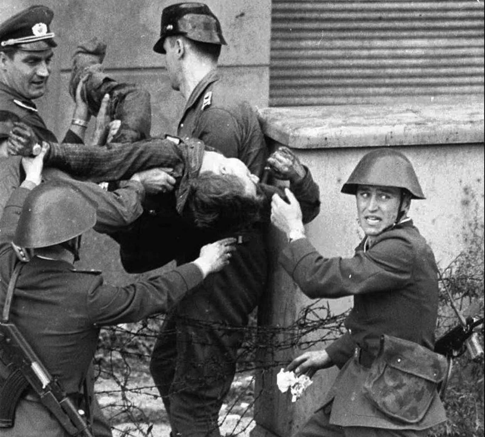A dying Peter Fechter is carried away by East German border guards who shot him down when he tried to flee to the West in this August 17, 1962, photo. Fechter was lying in no-man's-land for 50 minutes before he was taken to a hospital, where he died shortly after his arrival.