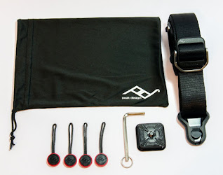 the box contains the strap, camera base plate, a hex key, 4 anchors and a small storage bag