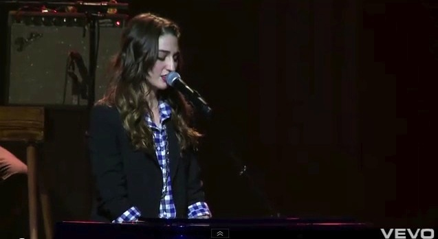 Sara Bareilles at keyboard in black jacket over blue-and-white checkered shirt