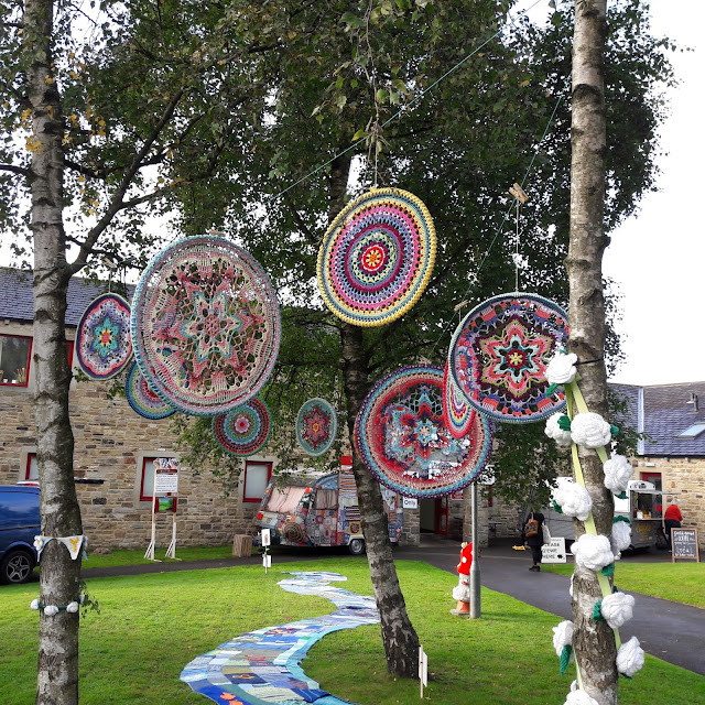 Multi-coloured circular crocheted mandalas hanging from the branches of trees