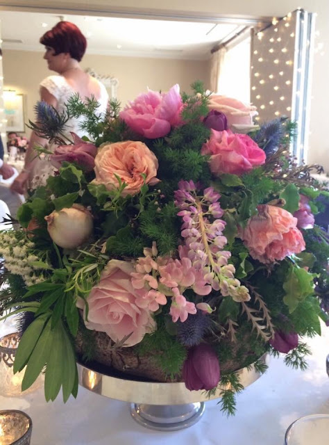 Wedding flower displays of pink and peach roses, purple tulips, lilac wysteria, pink peonies and blue thistles at British outdoor wedding
