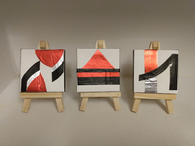 Three miniature foil-decorated canvasses, each on a wooden easel. Color scheme of silver, black, red, and white.