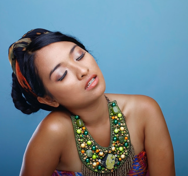 Pretty Asian girl wearing a traditional bib-type beaded necklace.