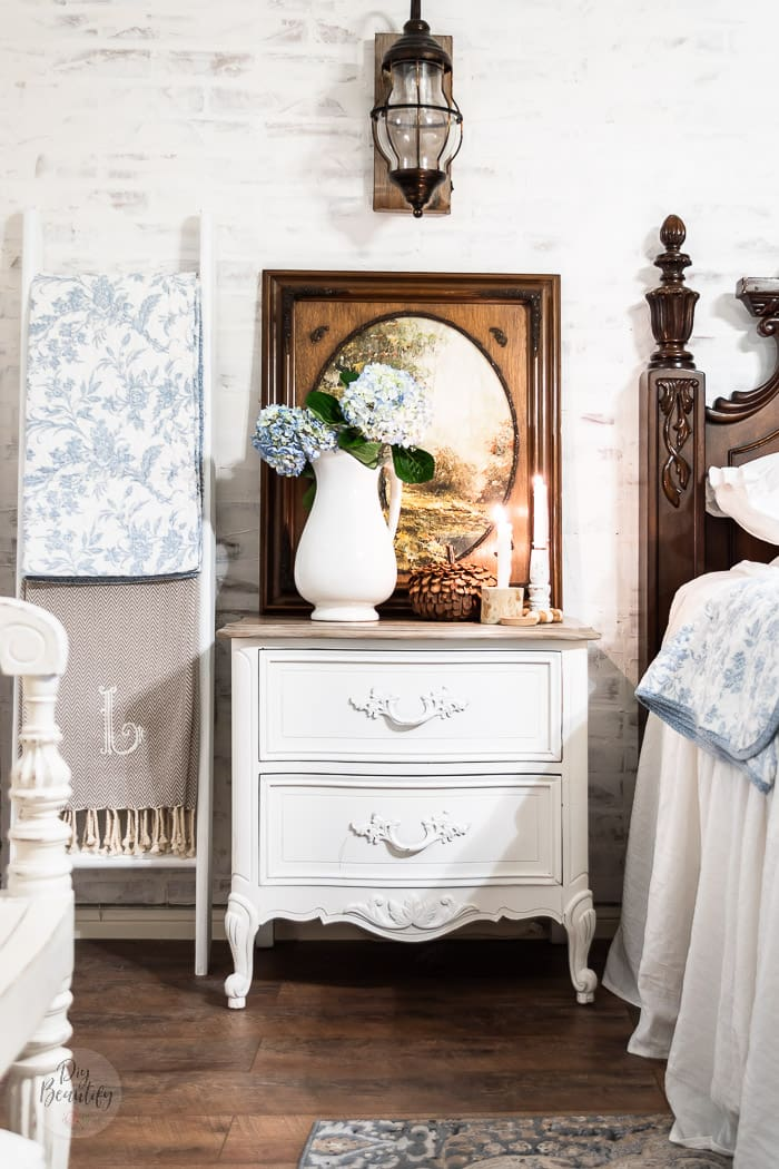 white brick wall, ladder with blankets, nightstand with hydrangeas in ironstone pitcher, candlesticks and rustic pumpkin