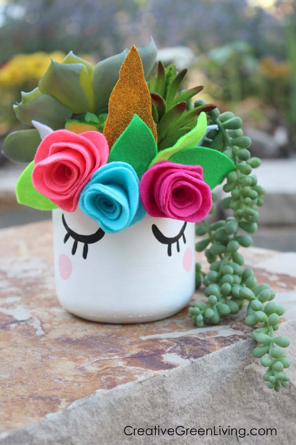 How to make a DIY unicorn mason jar succulent planter with a flower crown. A group of these would make the perfect centerpiece and favor for birthday parties! This craft tutorial even comes with a free downloadable unicorn horn and flower crown pattern to make it easy to make! #unicorn #unicorncrafts #masonjar #masonjarcrafts #succulents
