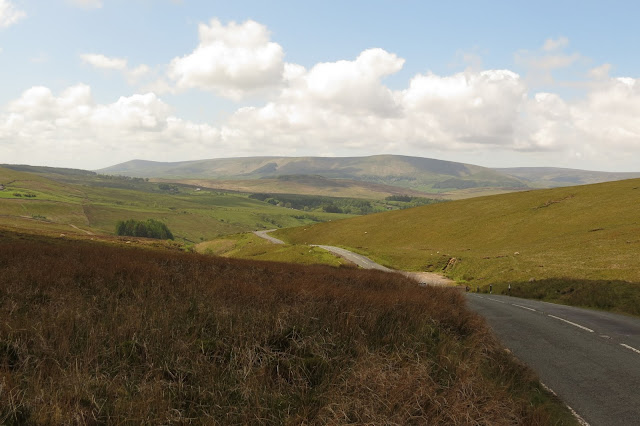 A country road with moorland on either side and high fells on the horizon.