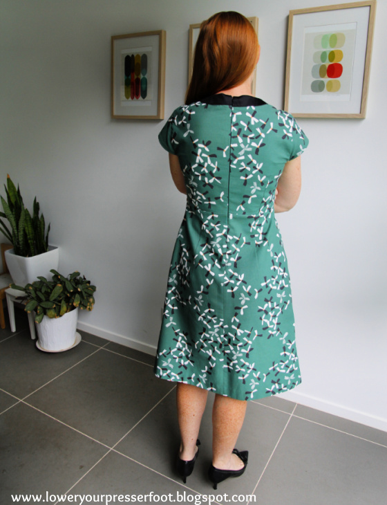a lady with red hair posing in a green dress with her back turned to the camera