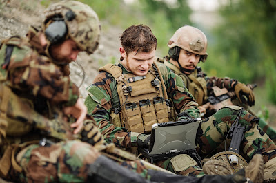 Pic of 3 soldiers with guns in the field, middle one on laptop communications