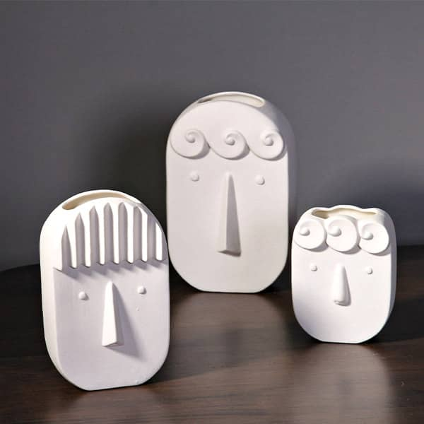 all-white head vases with sharp facial features