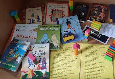 W gablocie znajduje się 9 książek oraz dwie żółte kartki ze spisem książek oraz kolorowe rozrzucone klocki.