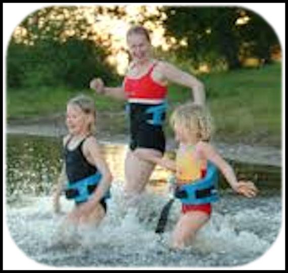 """Pari """"uimakouluikäistä"""" lasta ja yksi aikuinen juoksevat vauhdilla rannalta veteen. Lapsilla vartalon ympärillä pinnalla pysymistä varmentavat """"kellunta-avut""""."""