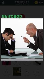 руководитель объявляет выговор мужчине сидящему за столом