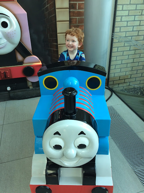 Little boy sitting in a ride on Thomas
