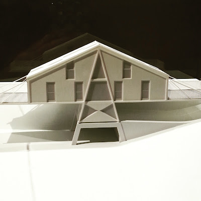 Close up of an architect's model of a modernist building in a perspex case.