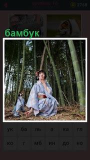 рядом с бамбуком сидит девушка в национальной одежде
