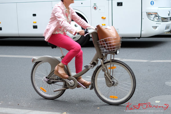 lady in all pink outfit brown wedge sandals and large leather bucket bag tote in handlebar basket, Vélib city bike. Paris photos by Kent Johnson for Street Fashion Sydney.