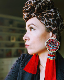 Woman with patterned head scarf and large red earrings.