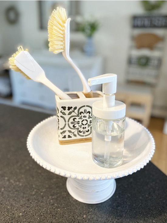 pedestal dish by the sink with brushes and soap