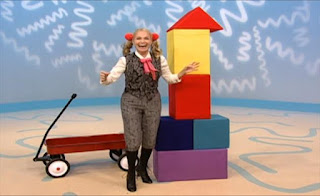 Ms. Noodle stacks the blocks and places the triangle on the top piece. Sesame Street Elmo's World Building Things The Noodle Family