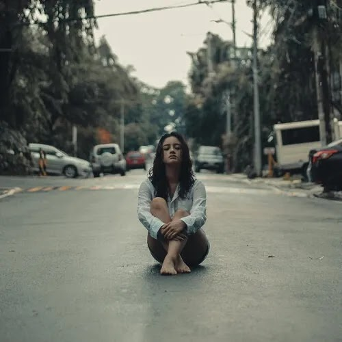 alone girl sitting middle of road