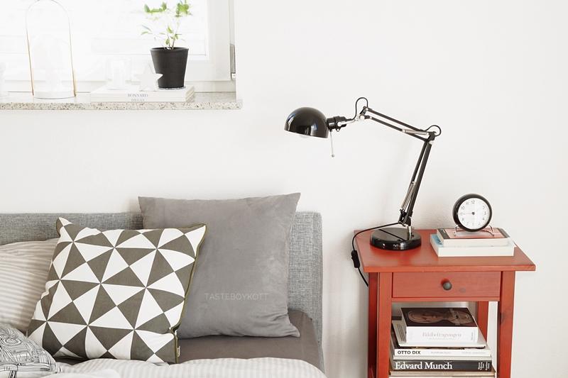 Schlafzimmer modern hell weiß-grau, roter Nachttisch als Farbtupfer. Ikea, Arne Jacobsen Wecker, Kopfteil Bett, Kissen geometrisch gemustert Ferm, Tischleuchte. Tasteboykott Blog Interior.