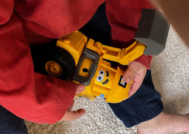 Close up of a 1 year old pushing the hard had down on the Construction Pal toy